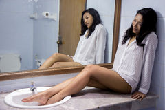 Woman resting in the bathroom. Woman with her feet in the sink in the bathroom sitting at the mirror royalty free stock photos