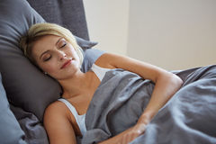 Woman resting in bed with hands beside her head Royalty Free Stock Images