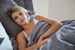 Woman resting in bed with hands beside her head Royalty Free Stock Photo