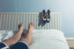Woman resting on bed after walking in high heels Royalty Free Stock Photo