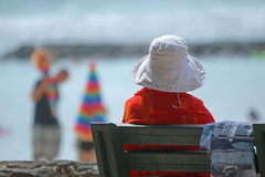 Woman Resting on Bench. Woman in orange jacket resting on a bench at the beach Stock Photos