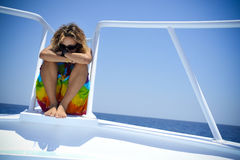 Woman resting on boat. Woman resting quietly on stern of boat on sunny day Stock Photos