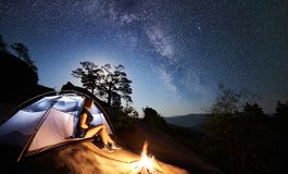 Woman resting beside camp, bonfire and tourist tent at night royalty free stock photography