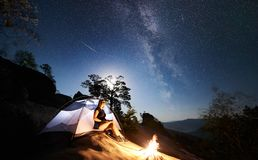 Woman resting beside camp, bonfire and tourist tent at night stock photography