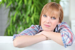 Woman resting on couch back Stock Images