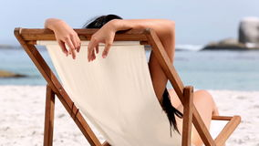 Woman resting on deck chair. On the beach stock video