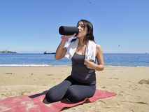 Woman resting and drinking after exercise Royalty Free Stock Photography