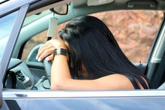 Woman resting after driving. Woman that sits on the wheel after driving stock photography