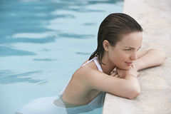 Woman Resting On The Edge Of Swimming Pool Stock Images