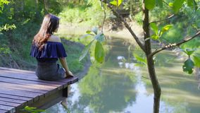 Woman resting on edge of wooden jetty. Woman resting on edge of a wooden jetty stock footage