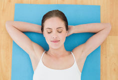 Woman resting on exercise mat with eyes closed Royalty Free Stock Photo