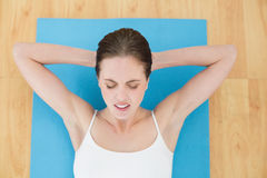 Woman resting on exercise mat with eyes closed Stock Images