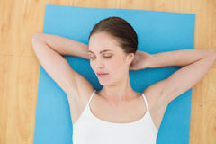 Woman resting on exercise mat Stock Photography