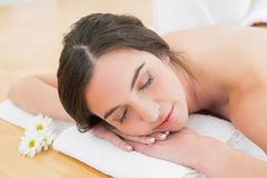 Woman resting with eyes closed on towel at beauty spa Stock Image