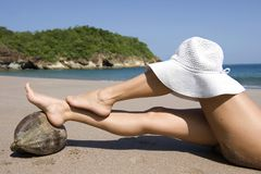 Woman resting feet coconut beach hat on knee. Woman resting legs on coconut on tropical beach with white hat on knee, guanacaste, costa rica, central america Stock Image