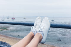 Woman resting feet on railing by the sea Stock Photos