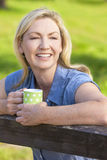 Woman Resting on Fence Drinking Tea or Coffee Stock Photos