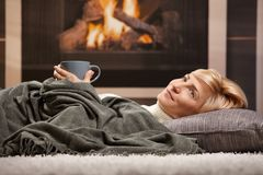 Woman resting beside fireplace Stock Photography