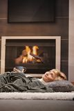 Woman resting beside fireplace. Woman resting at home lying on floor in front of a fire place stock images
