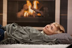 Woman resting beside fireplace. Woman resting at home lying on floor in front of a fire place royalty free stock photo