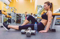 Woman resting and friend doing dumbbells exercises Royalty Free Stock Photo