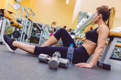 Woman resting and friend doing dumbbells exercises Stock Photo