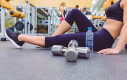 Woman resting and friend doing dumbbells exercises Royalty Free Stock Images