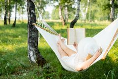 Woman resting in hammock outdoors. Relax and reading the book. Woman resting in hammock outdoors. Relax and reading the book royalty free stock photos