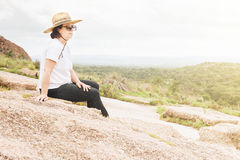 Woman Resting Happily on a Rock Outcropping Stock Images