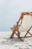 Woman resting on her deck chair in front of ocean Royalty Free Stock Photo