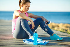 Woman resting after jogging on a wooden path at the sea Stock Images