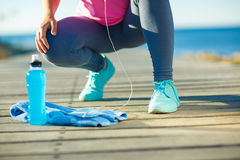 Woman resting after jogging on a wooden path at the sea Stock Photography