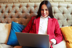 Woman resting with laptop on sofa Stock Image