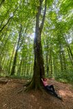 Woman resting after a long hike. Hiker woman resting against a big tree in the forest Royalty Free Stock Images