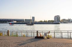 Woman resting lying on the Amstel River shore against the backdrop of the port and Central Station in Amsterdam royalty free stock photography