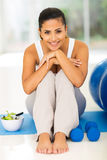 Woman resting mat. Happy young woman resting on mat after exercise at home Royalty Free Stock Images