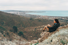 Woman resting in the mountains over the town Royalty Free Stock Images