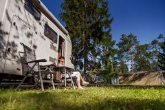 Woman resting near motorhomes in nature. Family vacation travel, holiday trip in motorhome RV, Caravan car Vacation. royalty free stock images