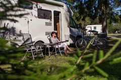 Woman resting near motorhomes in nature. Family vacation travel, holiday trip in motorhome RV, Caravan car Vacation. stock images