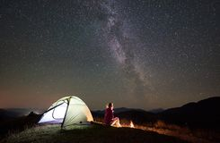 Woman resting at night camping in mountains under starry sky royalty free stock images