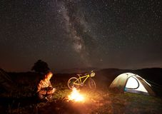 Woman resting at night camping near campfire, tourist tent, bicycle under evening sky full of stars royalty free stock image