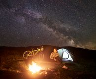 Woman resting at night camping near campfire, tourist tent, bicycle under evening sky full of stars royalty free stock images