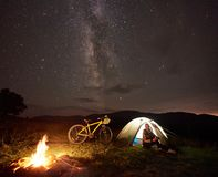 Woman resting at night camping near campfire, tourist tent, bicycle under evening sky full of stars. Young woman cyclist enjoying at night camping near burning royalty free stock photos