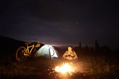 Woman resting at night camping near campfire, tourist tent, bicycle under evening sky full of stars stock image