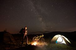 Woman resting at night camping near campfire, tourist tent, bicycle under evening sky full of stars stock images