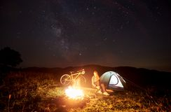 Woman resting at night camping near campfire, tourist tent, bicycle under evening sky full of stars. Young woman traveller having a rest at night camping near stock image