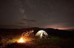 Woman resting at night camping near campfire, tourist tent, bicycle under evening sky full of stars. Young woman traveller having a rest at night camping near royalty free stock photo