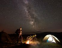 Woman resting at night camping near campfire, tourist tent, bicycle under evening sky full of stars. Young woman cyclist having a rest at night camping near stock image