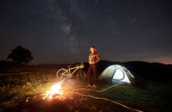 Woman resting at night camping near campfire, tourist tent, bicycle under evening sky full of stars. Young woman cyclist resting at night camping near burning royalty free stock image