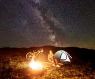 Woman resting at night camping near campfire, tourist tent, bicycle under evening sky full of stars. Young woman tourist having a rest at night camping near royalty free stock photo